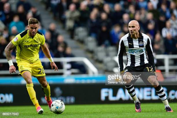 Jonjo Shelvey of Newcastle United and Michael Kightly of Burton Albion look to chase the ball during the Sky Bet Championship Match between Newcastle...