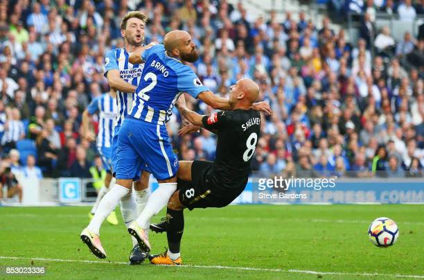 Jonjo Shelvey of Newcastle United collides with Dale Stephens and Bruno Saltor of Brighton and Hove Albion during the Premier League match between...