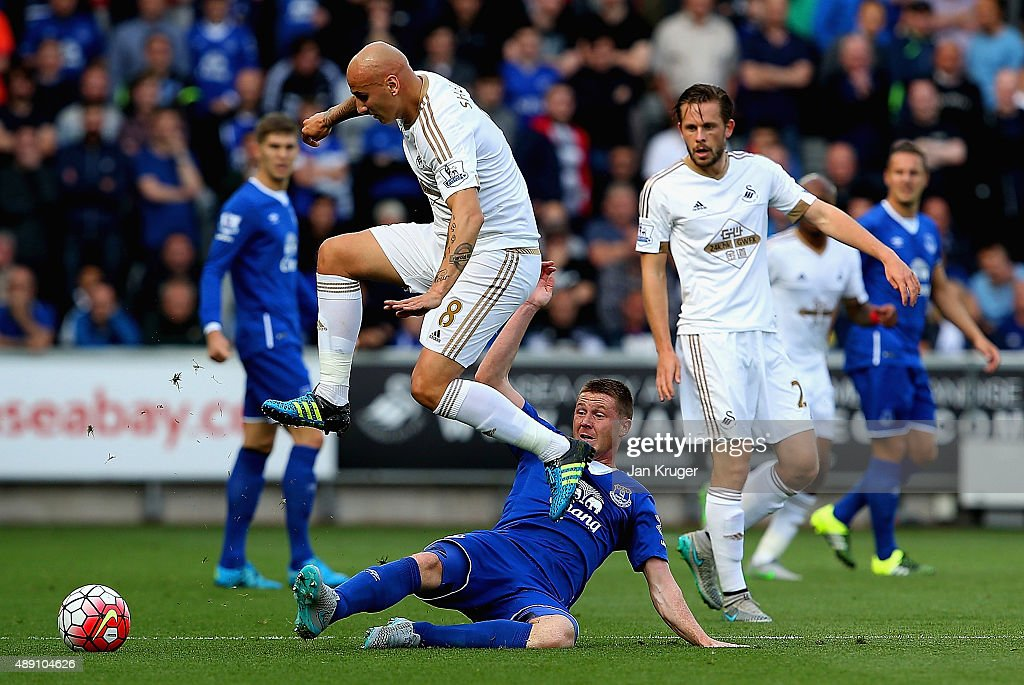 <a gi-track='captionPersonalityLinkClicked' href=/galleries/search?phrase=Jonjo+Shelvey&family=editorial&specificpeople=4940315 ng-click='$event.stopPropagation()'>Jonjo Shelvey</a> of Swansea City is tackled by <a gi-track='captionPersonalityLinkClicked' href=/galleries/search?phrase=James+McCarthy+-+Soccer+Player&family=editorial&specificpeople=8984734 ng-click='$event.stopPropagation()'>James McCarthy</a> of Everton during the Barclays Premier League match between Swansea City and Everton at the Liberty Stadium on September 19, 2015 in Swansea, United Kingdom.