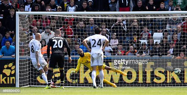 Jonjo Shelvey of Swansea puts the penalty away past Everton goalkeeper Tim Howard during the Barclays Premier League match between Swansea City and...