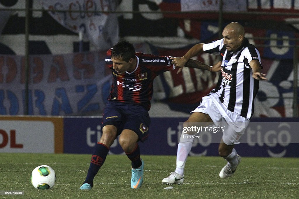 Jonnathan Fabbro (R) of Cerro Porteño and Pablo Guiñazu (L) fight for the ball during the match between Libertad and Cerro Porteño for the Aperture APF, at Defensores del Chaco on March 03, 2013 in Asuncion, Paraguay.