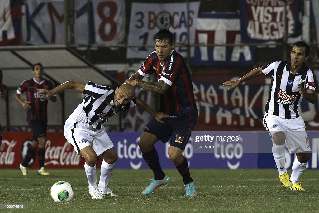 Jonnathan Fabbro (C) of Cerro Porteño, Pablo Guiñazu (L) and Sergio Aquino (R) fight for the ball during the match between Libertad and Cerro Porteño for the Aperture APF, at Defensores del Chaco on March 03, 2013 in Asuncion, Paraguay.