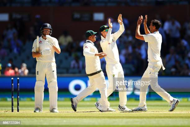 Jonny Bairstow of England looks dejected as Usman Khawaja Cameron Bancroft and Mitchell Starc of Australia celebrate his wicket giving them victory...