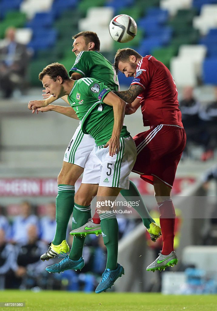 Jonny Evans (L) and Gareth McAuley (2nd L) of Northern Ireland jump with XXXTamas Kadar (R) of Hungary during the Euro 2016 Group F qualifying match at Windsor Park on September 7, 2015 in Belfast, Northern Ireland.
