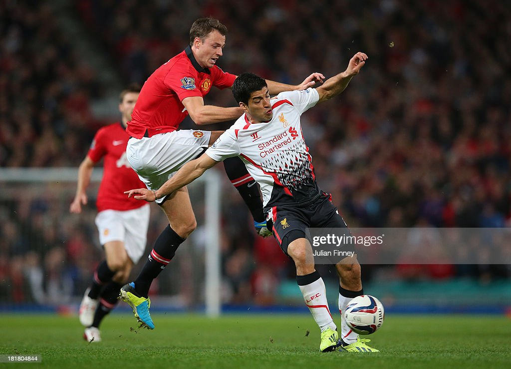 Jonny Evans of Manchester United competes with Luis Suarez of Liverpool during the Capital One Cup Third Round match betwen Manchester United and Liverpool at Old Trafford on September 25, 2013 in Manchester, England.