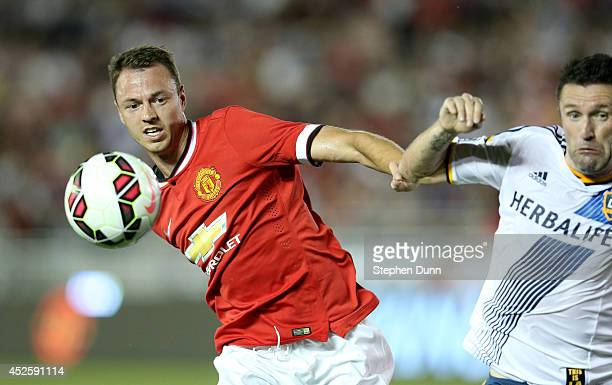 Jonny Evans of Manchester United fights for the ball with Robbie Keane of the Los Angeles Galaxy at the Rose Bowl on July 23 2014 in Pasadena...