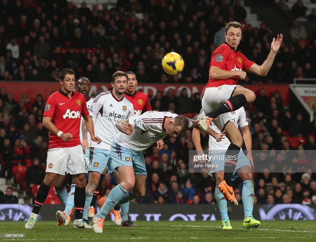 <a gi-track='captionPersonalityLinkClicked' href=/galleries/search?phrase=Jonny+Evans&family=editorial&specificpeople=747537 ng-click='$event.stopPropagation()'>Jonny Evans</a> of Manchester United in action with <a gi-track='captionPersonalityLinkClicked' href=/galleries/search?phrase=George+McCartney&family=editorial&specificpeople=240151 ng-click='$event.stopPropagation()'>George McCartney</a> of West Ham United during the Barclays Premier League match between Manchester United and West Ham United at Old Trafford on December 21, 2013 in Manchester, England.