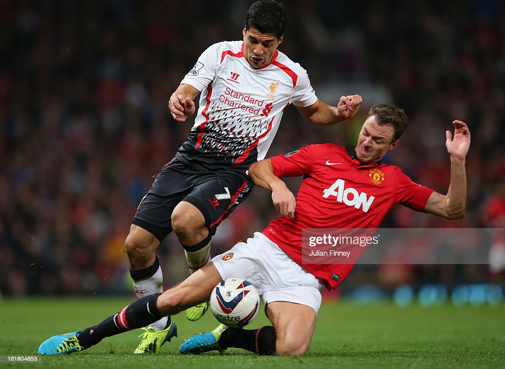 Jonny Evans of Manchester United tackles Luis Suarez of Liverpool during the Capital One Cup Third Round match betwen Manchester United and Liverpool at Old Trafford on September 25, 2013 in Manchester, England.