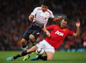 Jonny Evans of Manchester United tackles Luis Suarez of Liverpool during the Capital One Cup Third Round match betwen Manchester United and Liverpool...