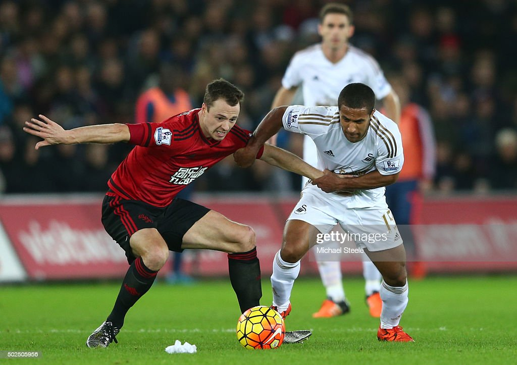 Jonny Evans of West Bromwich Albion and Wayne Routledge of Swansea City battle for the ball during the Barclays Premier League match between Swansea City and West Bromwich Albion at the Liberty Stadium on December 26, 2015 in Swansea, Wales.