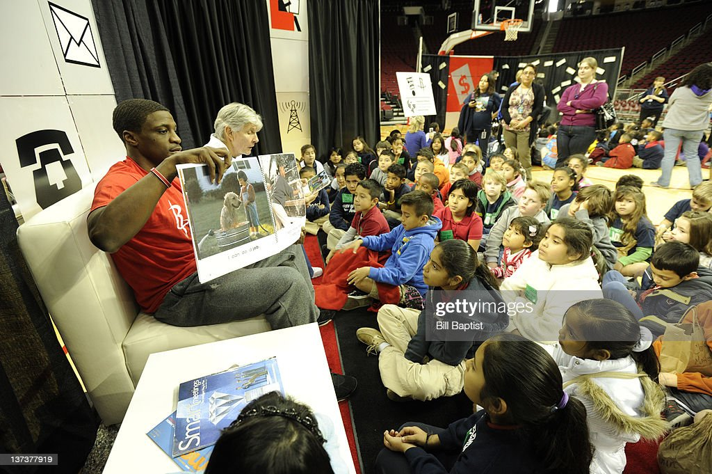 Jonny Flynn #9 of the Houston Rockets reads to children during Read Play Win on January 18, 2012 at the Toyota Center in Houston, Texas.
