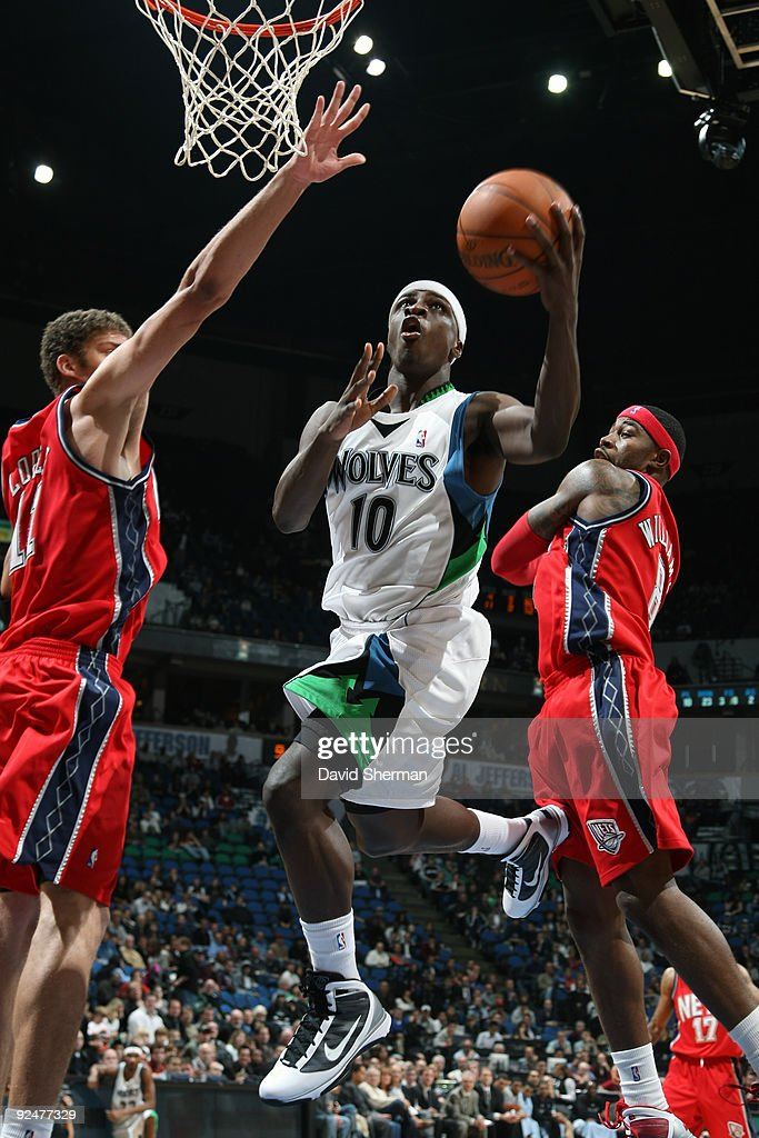 Jonny Flynn #10 of the Minnesota Timberwolves splits the defense against Brook Lopez #11 and Terrence Williams #8 of the New Jersey Nets during the season opening game on October 28, 2009 at the Target Center in Minneapolis, Minnesota.