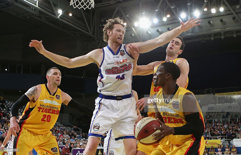 Jonny Flynn of the Tigers controls the ball as Luke Schenscher of the 36ers defends during the NBL match between the Melbourne Tigers and the...