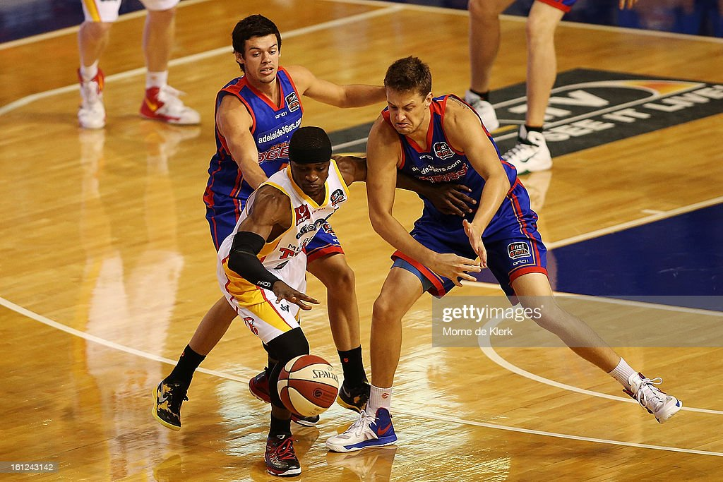 Jonny Flynn of the Tigers is put under pressure by Jason Cadee and Daniel Johnson of the 36ers during the round 18 NBL match between the Adelaide 36ers and the Melbourne Tigers at Adelaide Arena on February 10, 2013 in Adelaide, Australia.