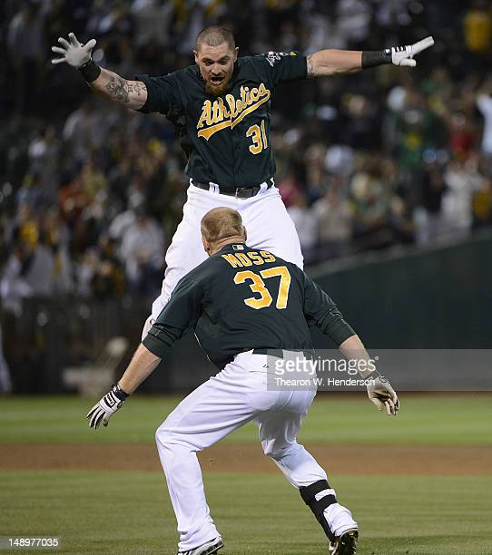 Jonny Gomes and Brandon Moss of the Oakland Athletics celebates after Moss hit an RBI single to drive in Yoenis Cespedes for a walkoff win in the...