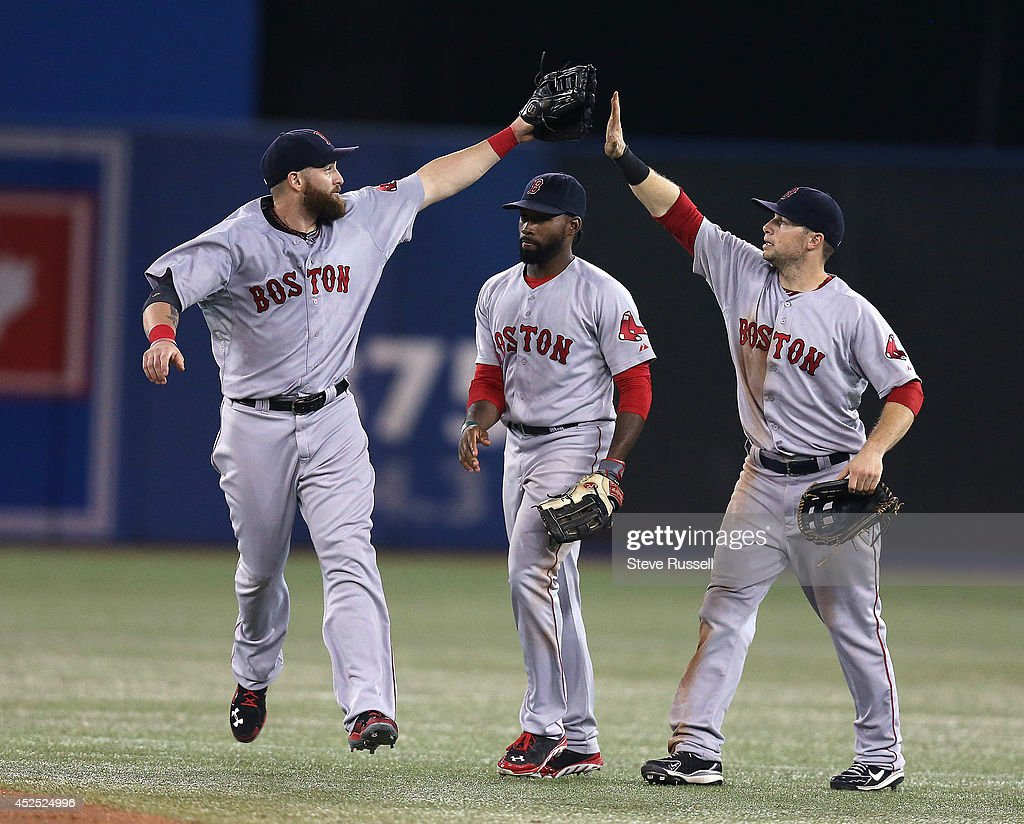 TORONTO, ON- JULY 21 - Jonny Gomes and Brock Holt tap gloves in front of Jackie Bradley Jr. as the Toronto Blue Jays lose the Boston Red Sox 14-1 in Rogers Centre in Toronto. July 21, 2014.