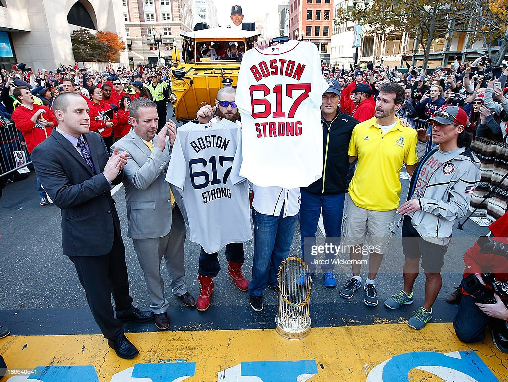 Jonny Gomes #5 and Jarrod Saltalamacchia #39 of the Boston Red Sox present the 'Boston Strong 617' jerseys to owners of two of the businesses at the bombing sites, including Shane O'Hara (second from right) and Dan Solo (R) on the finish line of the Boston Marathon on Boylston Street during the World Series victory parade on November 2, 2013 in Boston, Massachusetts.