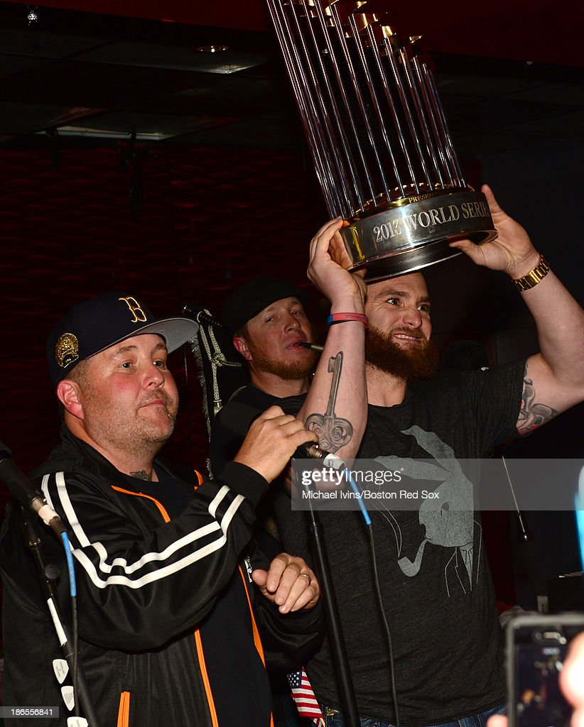 Jonny Gomes of the Boston Red Sox holds the World Series Trophy while singing along to 'The Boys Are Back' with the Dropkick Murphy's at a party...