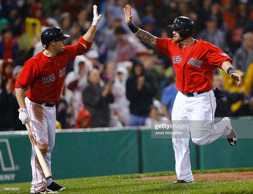 Jonny Gomes #5 of the Boston Red Sox is congratulated by teammate Daniel Nava #29 after scoring in the seventh inning against the Cleveland Indians during the game on May 24, 2013 at Fenway Park in Boston, Massachusetts.