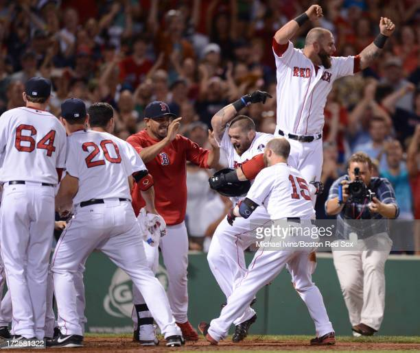 Jonny Gomes of the Boston Red Sox is mobbed by teammates after hitting a walkoff home run against the San Diego Padres in the ninth inning on July 3...