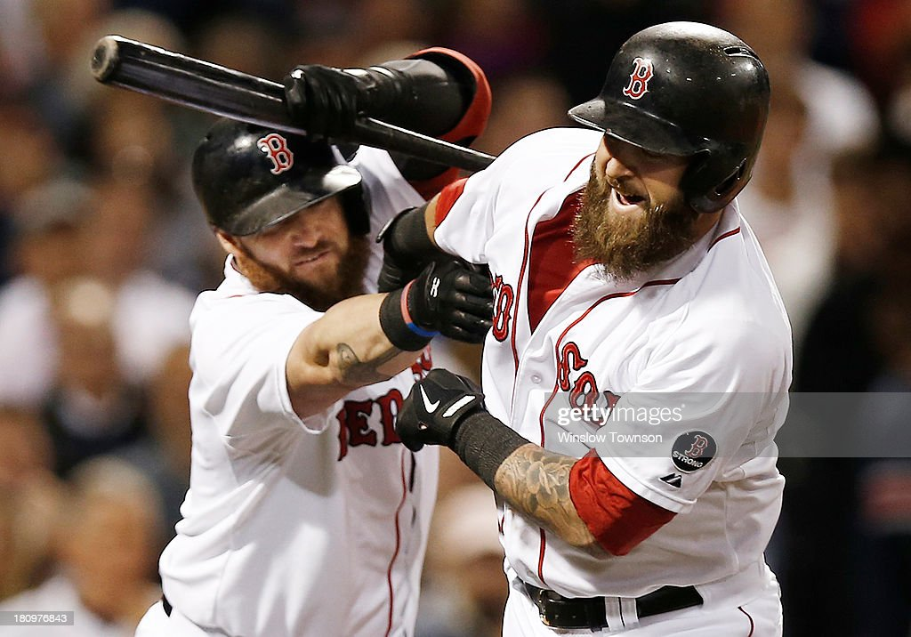 Jonny Gomes #5 of the Boston Red Sox, left, tries to pull the beard of Mike Napoli #12 of the Boston Red Sox after Napoli homered during the sixth inning of the game against the Baltimore Orioles at Fenway Park on September 18, 2013 in Boston, Massachusetts.