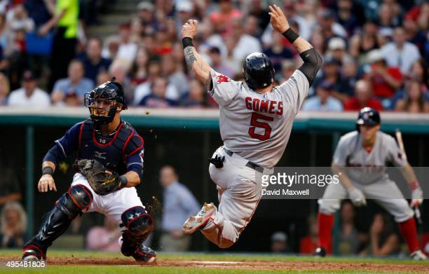 Jonny Gomes of the Boston Red Sox scores on a single by Jonathan Herrera as Cleveland Indians catcher Yan Gomes awaits the throw during the sixth...