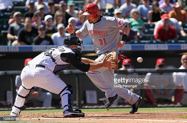 Jonny Gomes of the Cincinnati Reds beats the ball and gets around catcher Chris Iannetta of the Colorado Rockies to score in the second inning at...