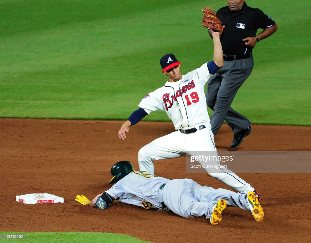 <a gi-track='captionPersonalityLinkClicked' href=/galleries/search?phrase=Jonny+Gomes&family=editorial&specificpeople=568435 ng-click='$event.stopPropagation()'>Jonny Gomes</a> #15 of the Oakland Athletics dives safely in to second base against <a gi-track='captionPersonalityLinkClicked' href=/galleries/search?phrase=Andrelton+Simmons&family=editorial&specificpeople=8978424 ng-click='$event.stopPropagation()'>Andrelton Simmons</a> #19 of the Atlanta Braves during the sixth inning at Turner Field on August 17, 2014 in Atlanta, Georgia.
