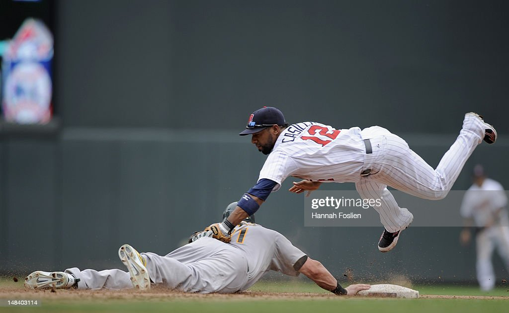 Jonny Gomes of the Oakland Athletics gets back to second base as Alexi Casilla of the Minnesota Twins looks to catch Gomes off base during the sixth...