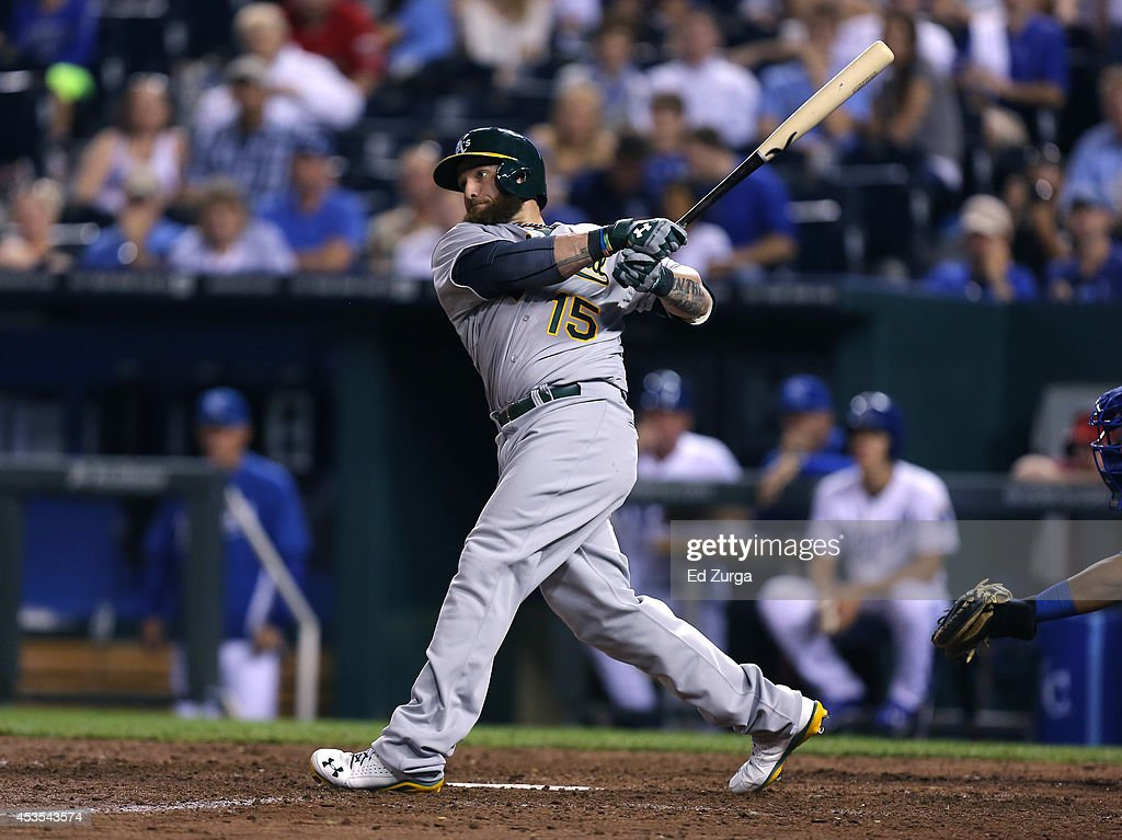 Jonny Gomes #15 of the Oakland Athletics hits a sacrifice fly in the eighth inning during a game against the Kansas City Royals at Kauffman Stadium on August 12, 2014 in Kansas City, Missouri.