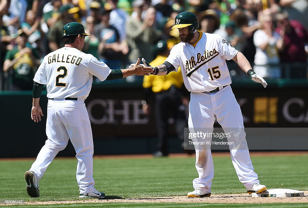 Jonny Gomes #15 of the Oakland Athletics is congratulated by third base coach Mike Gallego #2 after Goames hit a bases loaded two-run single against the Kansas City Royals in the bottom of the fifth inning at O.co Coliseum on August 2, 2014 in Oakland, California. Gomes went to third on a fielding error by left fielder Alex Gordon.