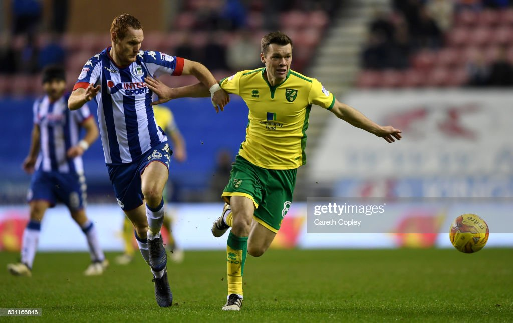 Jonny Howson of Norwich holds off Shaun MacDonald of Wigan during the Sky Bet Championship match between Wigan Athletic and Norwich City at DW Stadium on February 7, 2017 in Wigan, England.