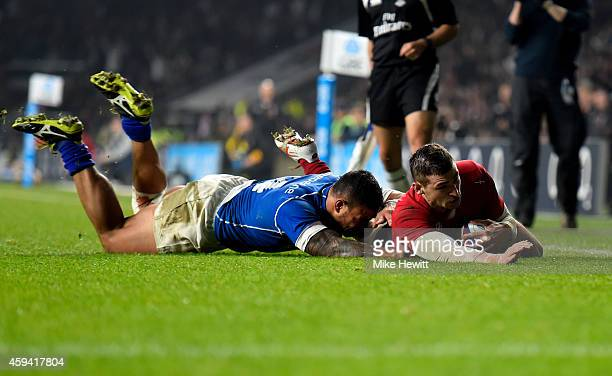 Jonny May of England scores his team's second try under pressure from Alapati Leiua of Samoa during the QBE international match between England and...