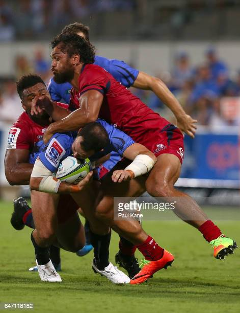 Jono Lance of the Force gets tackled by Samu Kerevi and Karmichael Hunt of the Reds during the round two Super Rugby match between the Western Force...