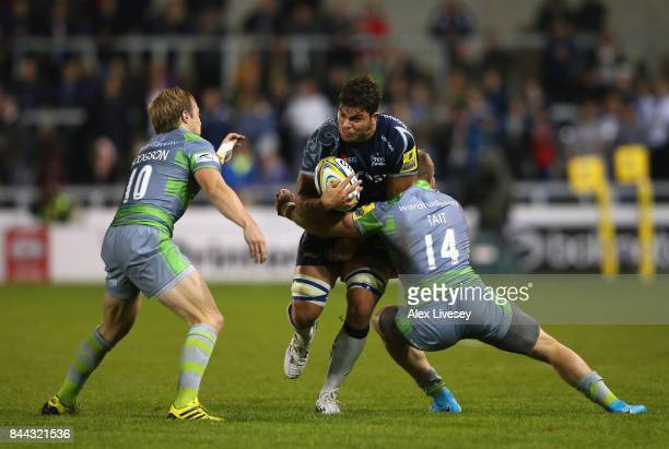 Jono Ross of Sale Sharks is tackled by Joel Hodgson and Alex Tait of Newcastle Falcons during the Aviva Premiership match between Sale Sharks and...