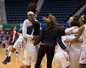 Jonquel Jones Lauren Chase Caira Washington and DaLacy Anderson of the George Washington Colonials celebrate their win against the Dayton Flyers in...
