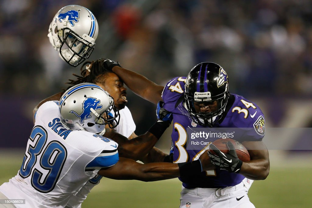 Jonte Green #36 of the Detroit Lions looses his helmet while being stiff armed by Bobby Rainey #34 of the Baltimore Ravens as Ricardo Silva #39 pushes him out of bounds during the first quarter at M&T Bank Stadium on August 17, 2012 in Baltimore, Maryland.