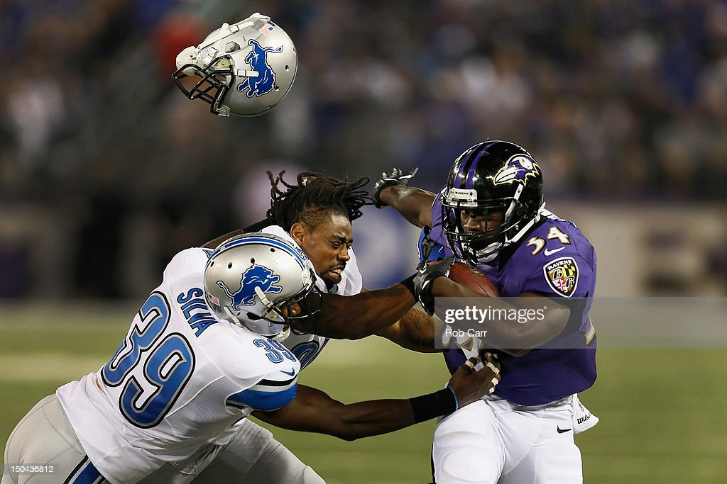 Jonte Green #36 of the Detroit Lions losses his helmet while being stiff armed by Bobby Rainey #34 of the Baltimore Ravens as Ricardo Silva #39 pushes him out of bounds during the first quarter at M&T Bank Stadium on August 17, 2012 in Baltimore, Maryland.
