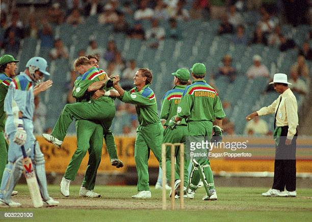 Jonty Rhodes of South Africa celebrates with teammates after the run out of Alec Stewart of England during the World Cup Zonal match between England...