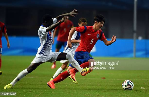 Joo Hwimin of Korea Republic runs past Amilton of Cape Verde Island during the 2014 Nanjing FIFA Summer Youth Olympic Boy's Football Tournament...
