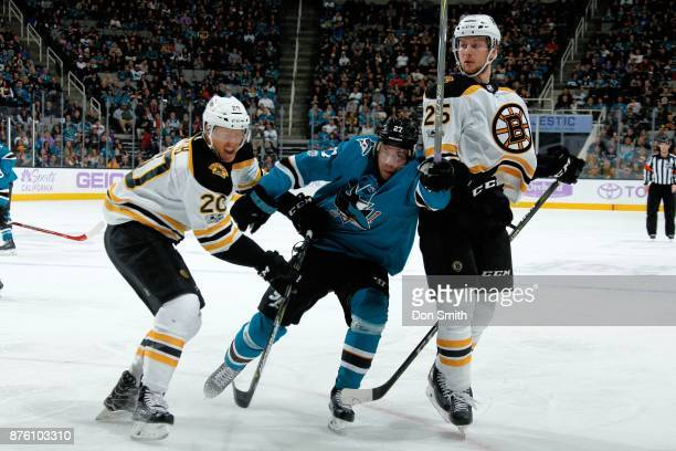 Joonas Donskoi of the San Jose Sharks is defended by Riley Nash and Brandon Carlo of the Boston Bruins at SAP Center on November 18 2017 in San Jose...