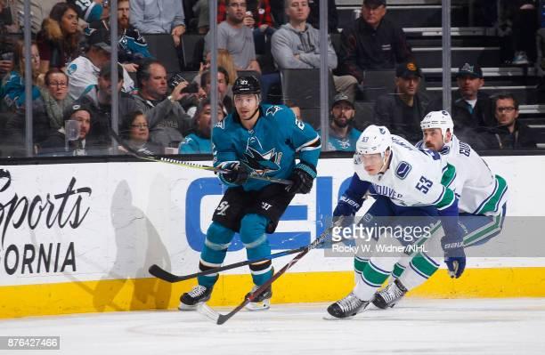Joonas Donskoi of the San Jose Sharks skates against Bo Horvat and Erik Gudbranson of the Vancouver Canucks at SAP Center on November 11 2017 in San...