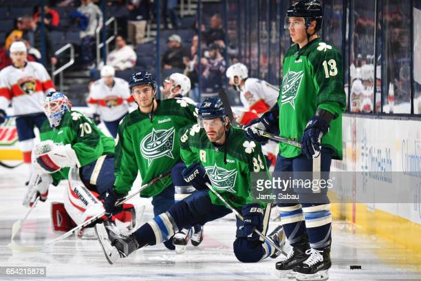 Joonas Korpisalo Alexander Wennberg Boone Jenner and Cam Atkinson all of the Columbus Blue Jackets warm up while wearing green jerseys in recognition...
