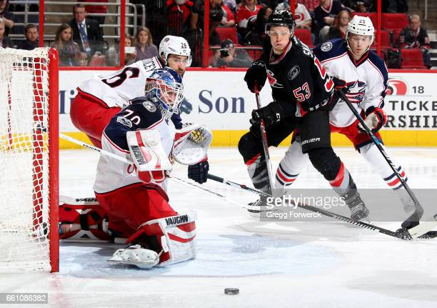 Joonas Korpisalo of the Columbus Blue Jackets deflects a puck as Jeff Skinner of the Carolina Hurricanes and William Karlsson skatee to the top of...