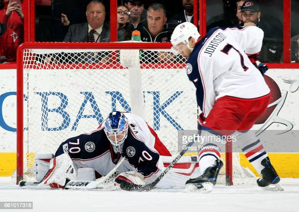 Joonas Korpisalo of the Columbus Blue Jackets dives on a loose puck as Jack Johnson guards the top of the crease during an NHL game against the...