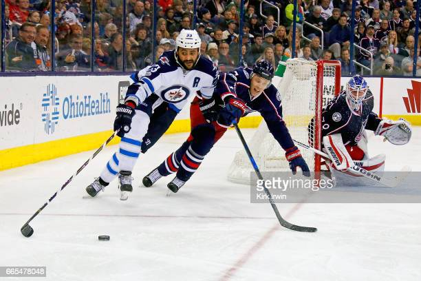 Joonas Korpisalo of the Columbus Blue Jackets follows the puck while Dustin Byfuglien of the Winnipeg Jets attempts to skate the puck around the net...