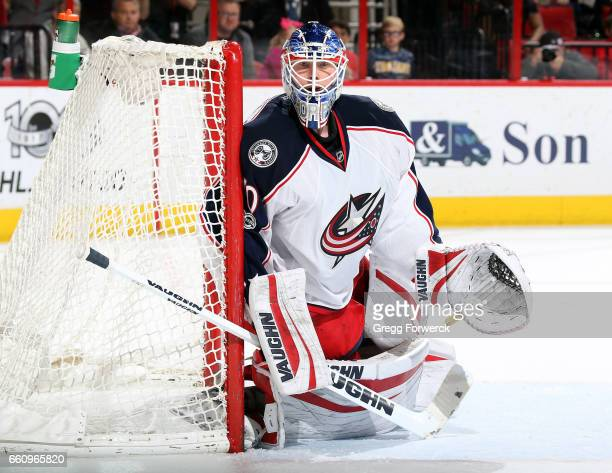 Joonas Korpisalo of the Columbus Blue Jackets guards the post as he watches a play develop during an NHL game against the Carolina Hurricanes on...