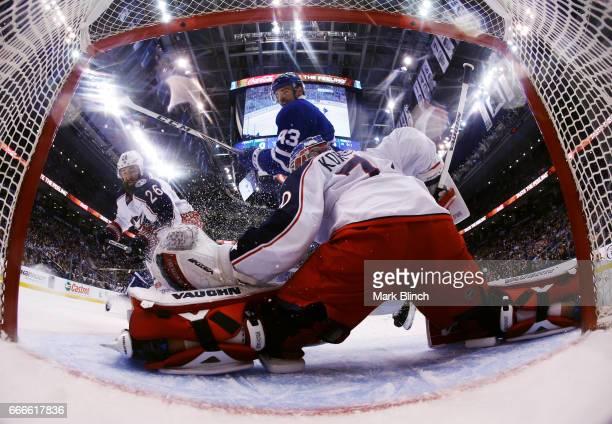 Joonas Korpisalo of the Columbus Blue Jackets makes a save as Nazem Kadri of the Toronto Maple Leafs and Kyle Quincey of the Columbus Blue Jackets...