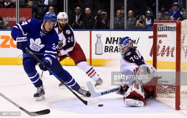 Joonas Korpisalo of the Columbus Blue Jackets makes a save on Auston Matthews of the Toronto Maple Leafs as Kyle Quincey of the Columbus Blue Jackets...