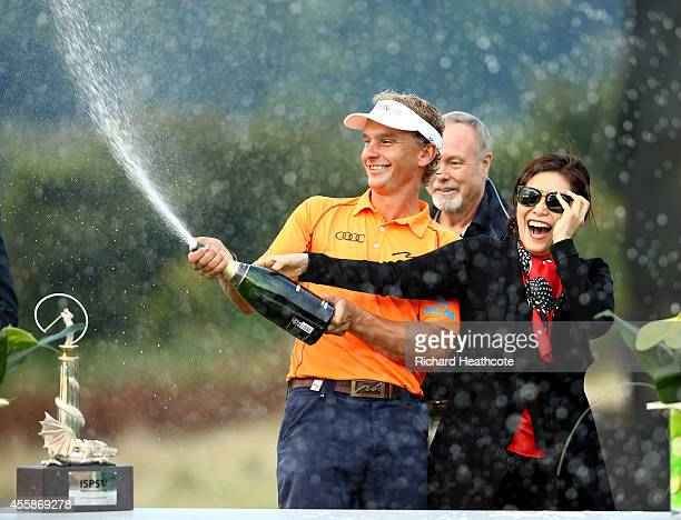 Joost Luiten of The Netherlands celebrates victory by spraying champagne with Midori Miyazaki ISPS Handa Executive Director of International Affairs...